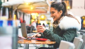 Beautiful and smiling young girl surfing on internet on her laptop while drinking a coffee - Stunning woman sitting outside in a cafe bar shopping online on her computer tablet booking holidays